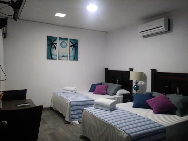 Habitación #2.- 2 camas matrimoniales, baño privado, A/C y televisión por cable.