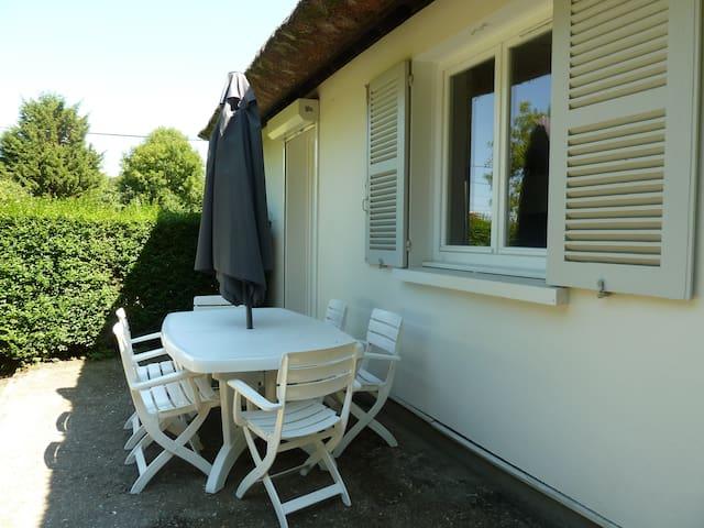 Terrasse avec salon de jardin, parasol et barbecue Weber