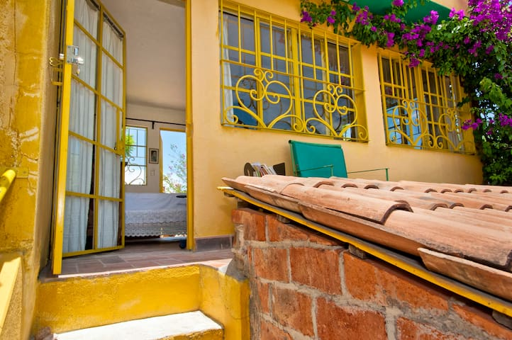 At the top of the stairs between the outside kitchen downstairs and the romantic roof bedroom with windows all around