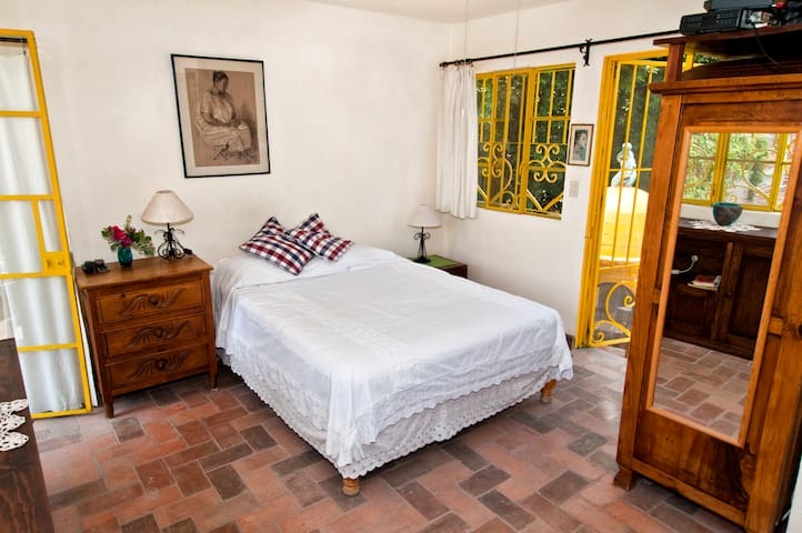 Roof bedroom, queen size bed, just before walking out onto the flowered terrace
