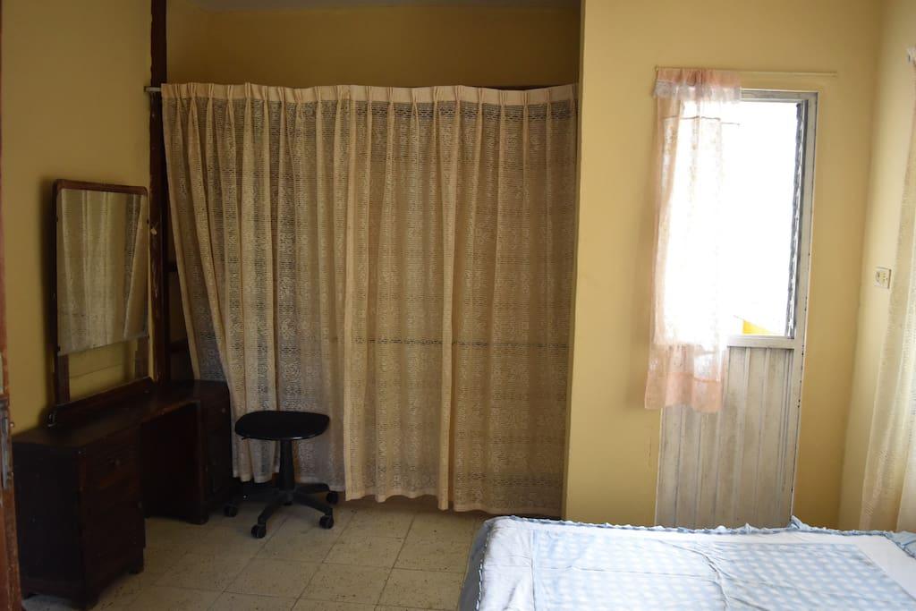 HABITACIÓN C.- Cuenta con un tocador con espejo, ropero amplio con ganchos en su interior, puerta con acceso a balcón, cama matrimonial.