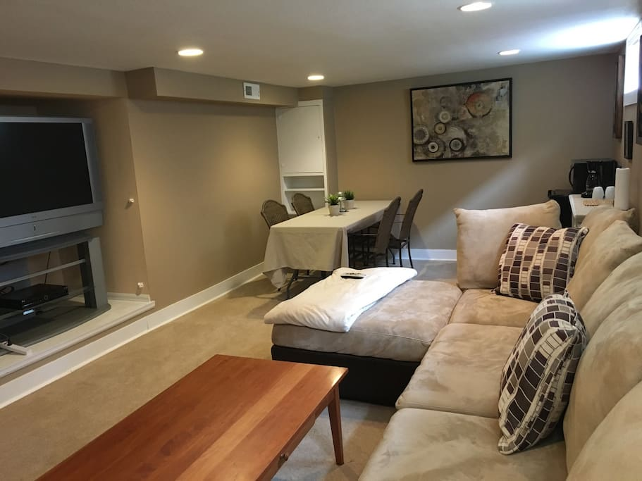 Large living area with tv, kitchenette, large sectional and seating for four people.