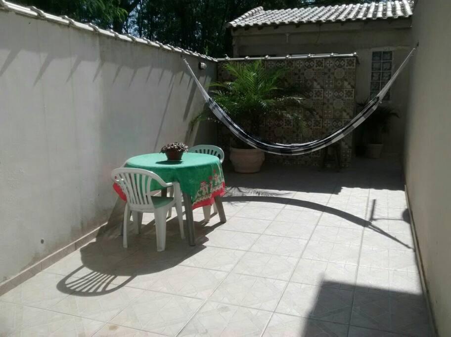 Quintal com rede, mesa e cadeira em área externa para café da manhã na área externa, jogos, bate papo.