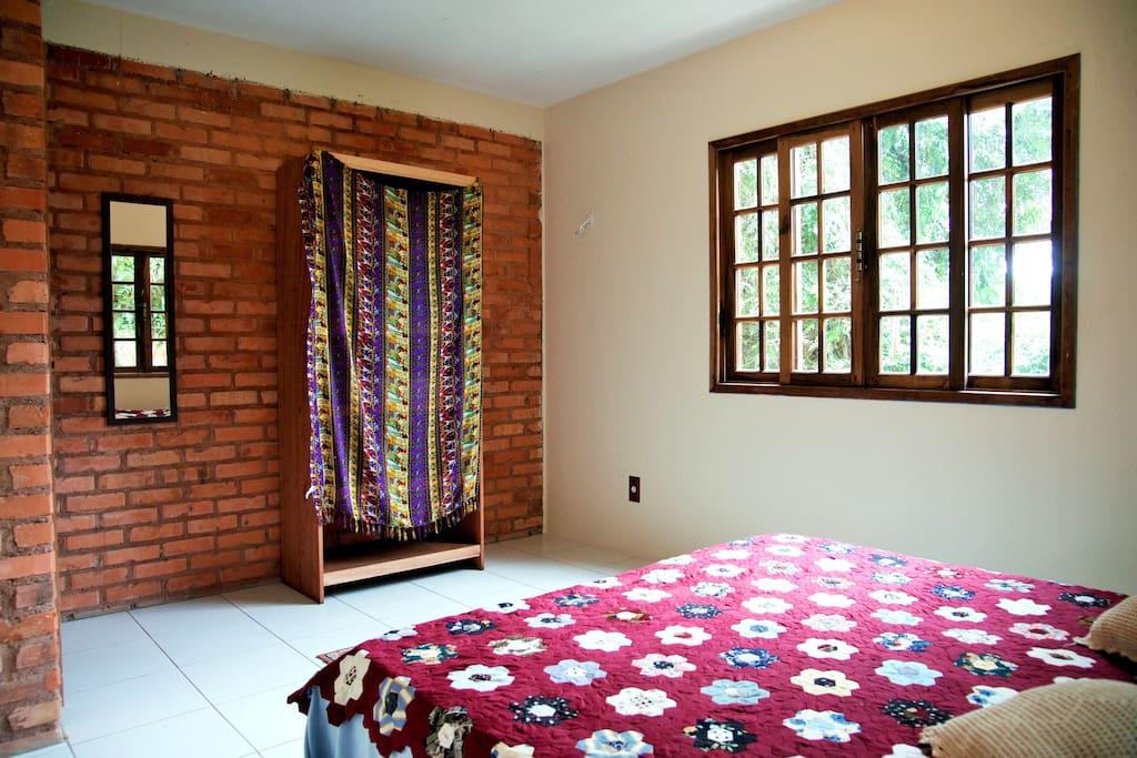 quarto com vistas para a janela, o armário e espelho