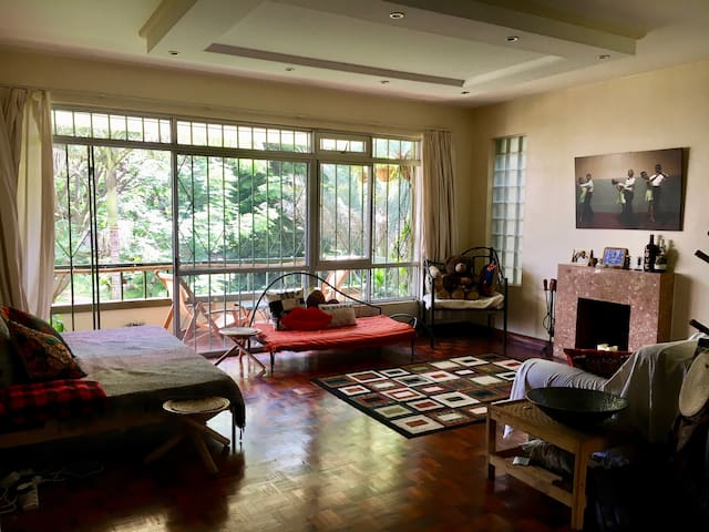 Living room with giant window and sliding door leading to balcony overlooking garden full of trees