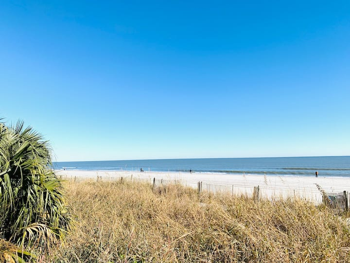 Step to the beach in this cute cabin style condo