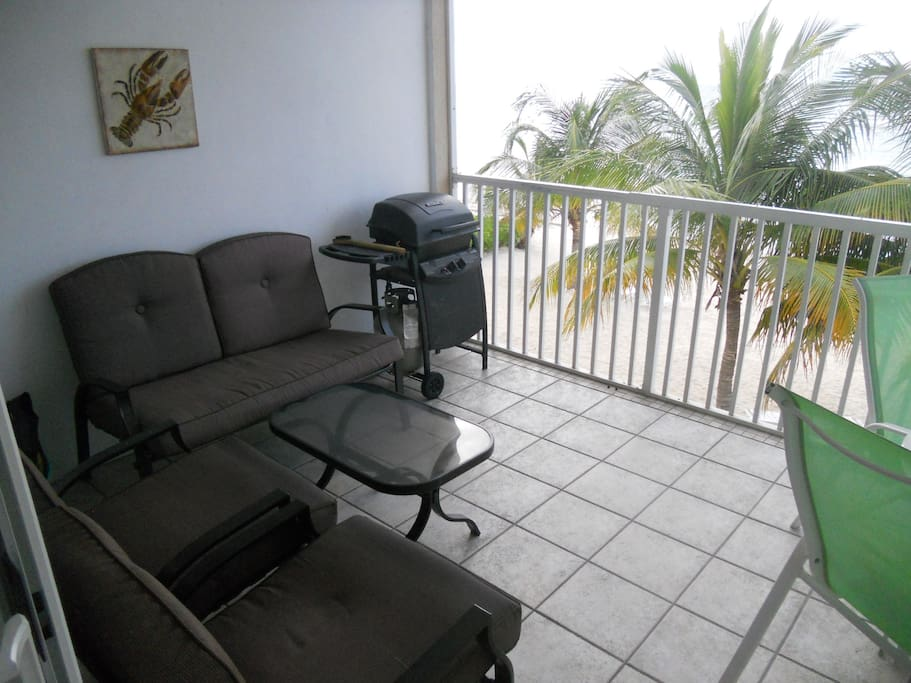 Lanai with patio furniture, Grill and dining table and Beachfront view