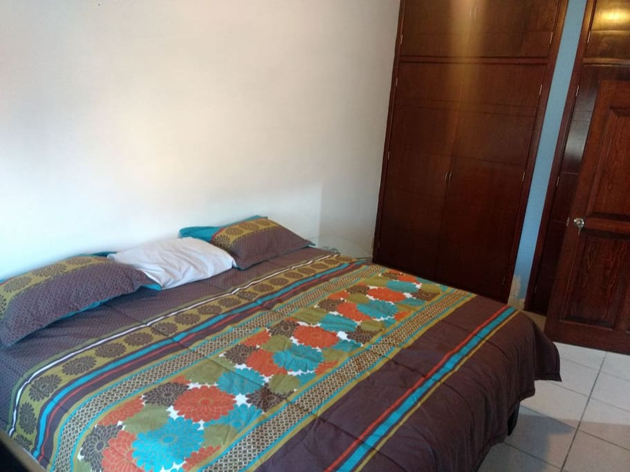 Cuarto principal con cama king size, closet y ventilador. Primary room with a king size bed, closet and fan.