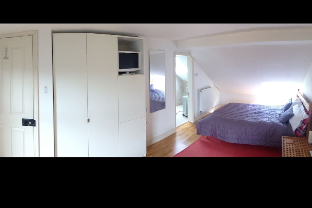 Large wardrobe with lots of storage space.  Television and door through to a small ensuite bathroom