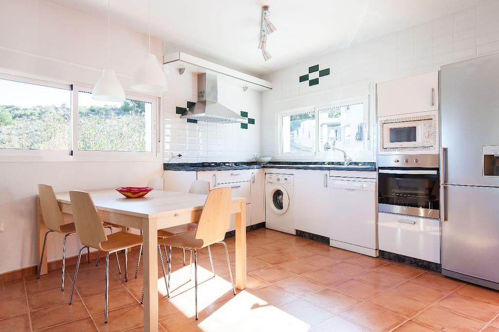La mesa del comedor con la cocina completamente equipada horno y lavavajillas incluidos