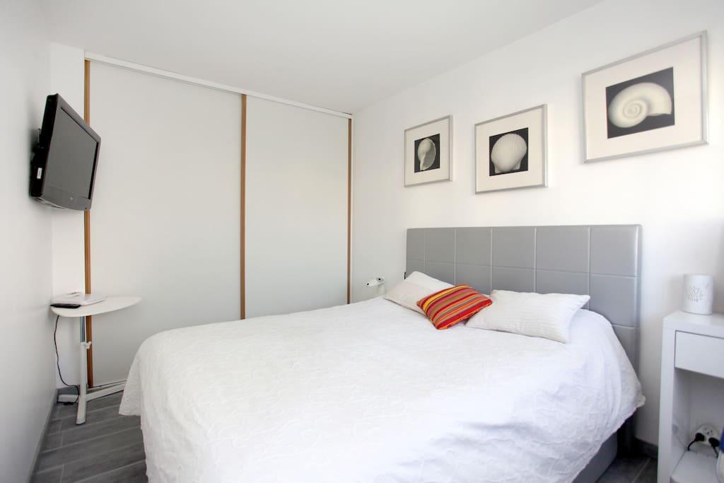 lit coffre king size et tv, chambre très claire