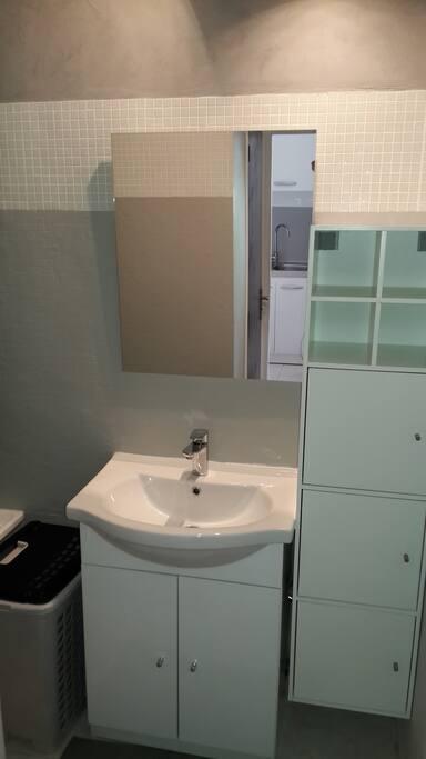 Salle de bain neuve et propre avec beaucoup de rangements.