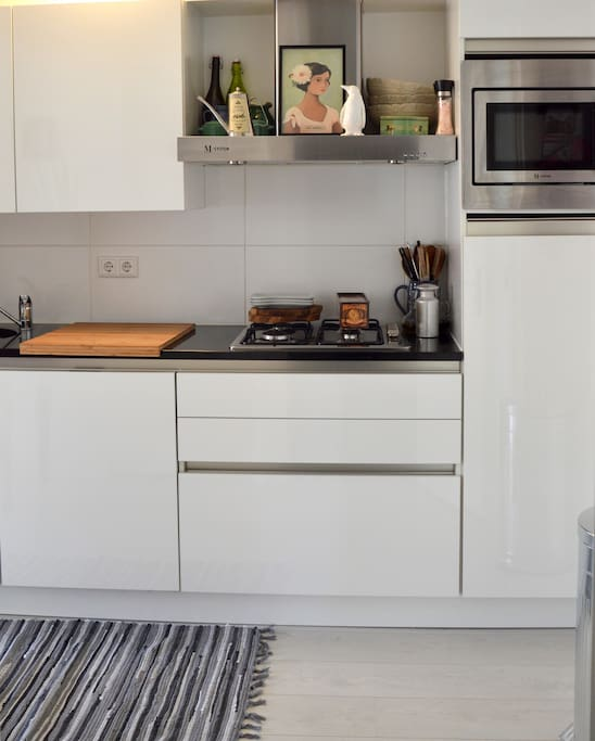 Fully equipped kitchen with dishwasher, microwave, oven, toaster and cooker.