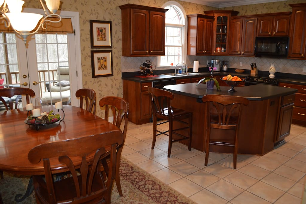 Open kitchen area with seating for 9 plus 6 more in dining room