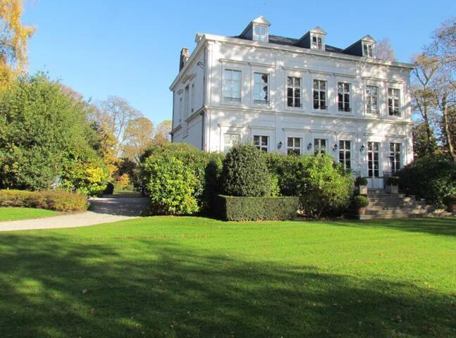 Façade arrière du Château avec sa terrasse qui domine le parc aux arbres centenaires.