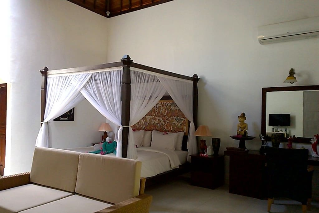 Air conditioned bed sitting room with romantic four poster bed and views to the garden.