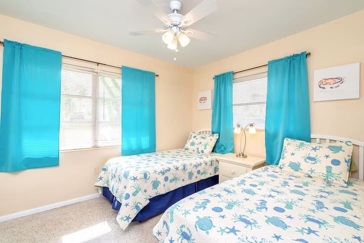 Bedroom 2 with matching twin beds and ceiling fan