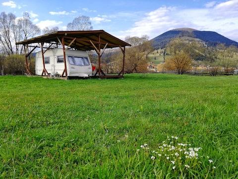 Уютный караван на лугу с видом на горы