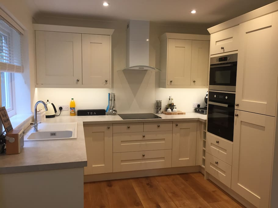 Kitchen with integrated fridge and freezer, oven, microwave oven and dishwasher.  An induction hob and lots of pans and utensils to cook with.