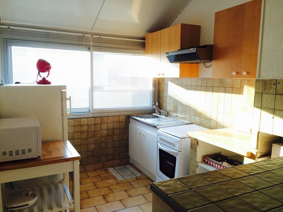 Fully equipped and well-lit kitchen with extractor fan + microwave + electric oven + toaster.