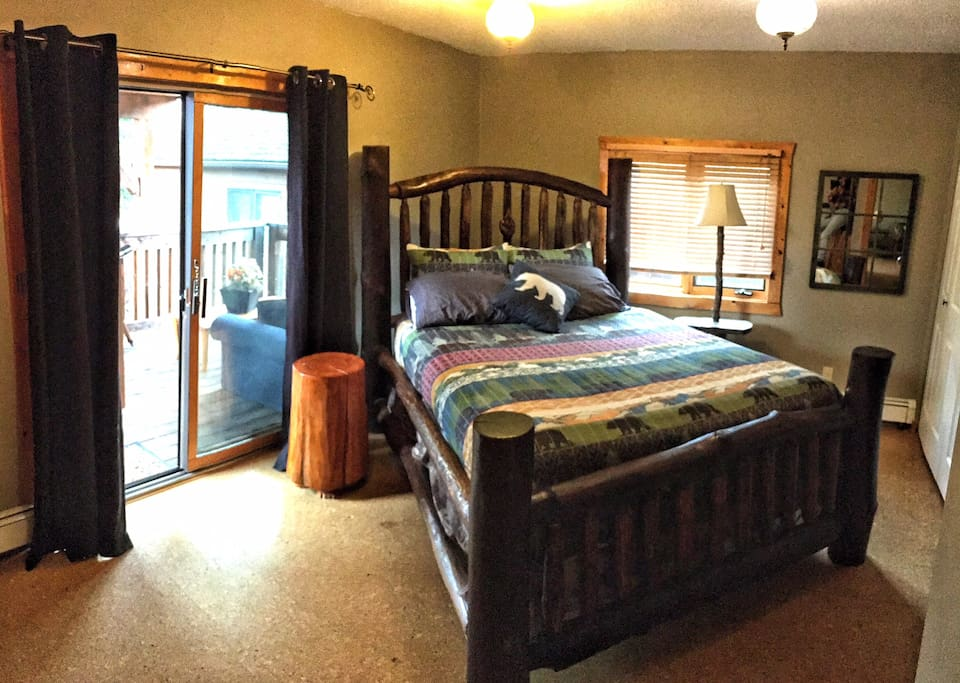 Spacious bedroom with custom log queen bed and patio door to private deck.