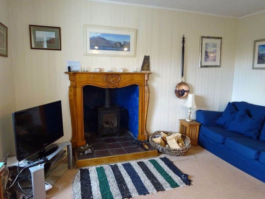 Living room with woodburner and traditional wood-lined walls
