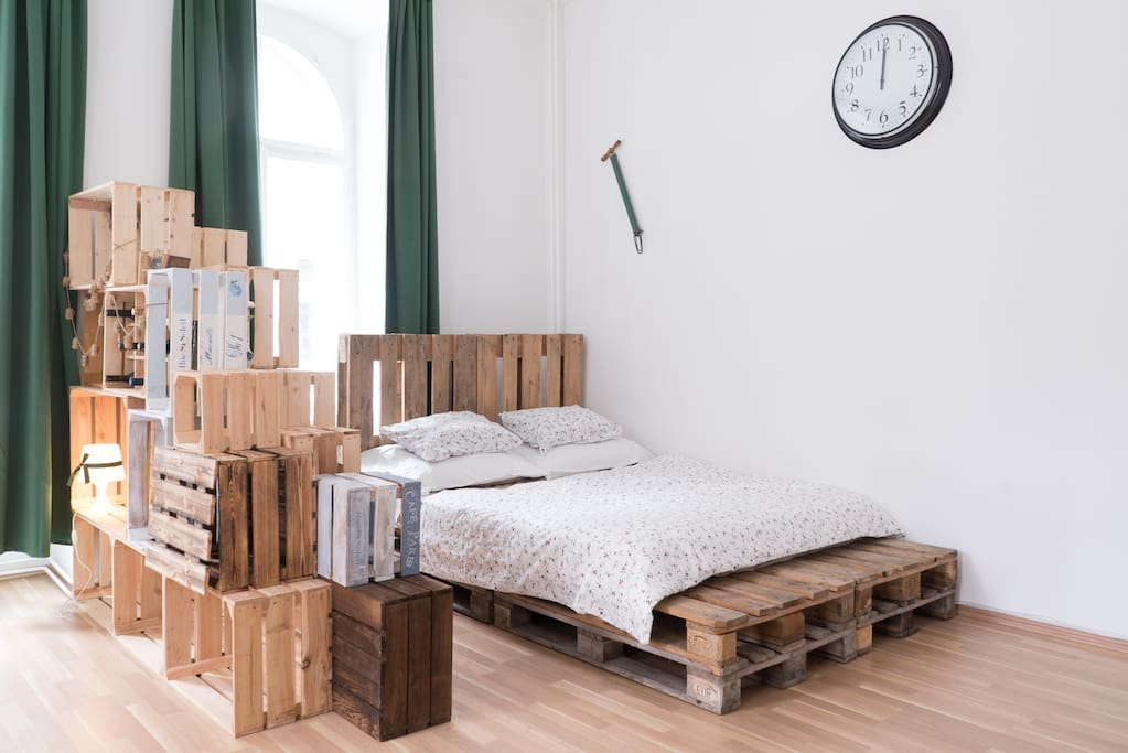 How about some nice sleep on this wooden double bed next to bunch of wooden shelfes?