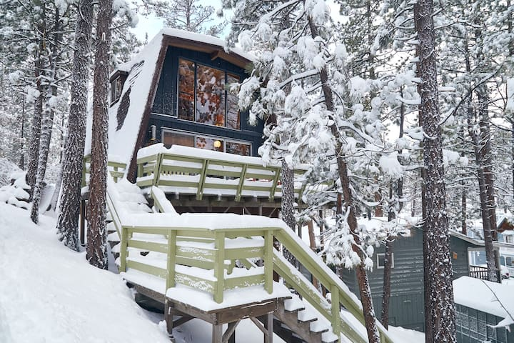 Treehouse Vibes just after a foot of snow. The cabin rests on a hill, making you feel like you're in a tree house. The trees that surround the cabin provide natural privacy. Please note the neighboring structure to the right.