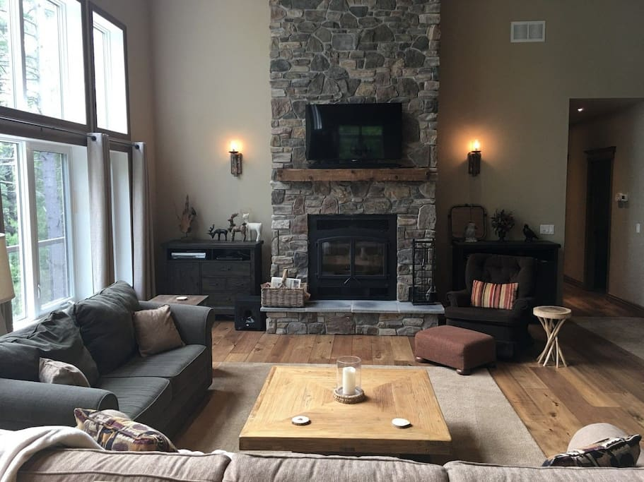 Floor-to-ceiling stone fireplace enhances the rustic ambience.
