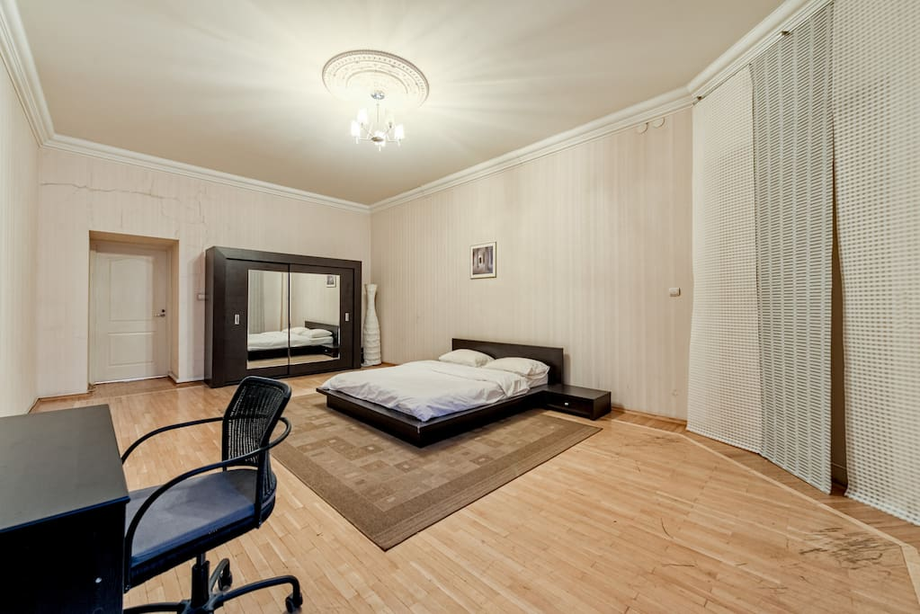 Bedroom with large wardrobe and desk and roling chair