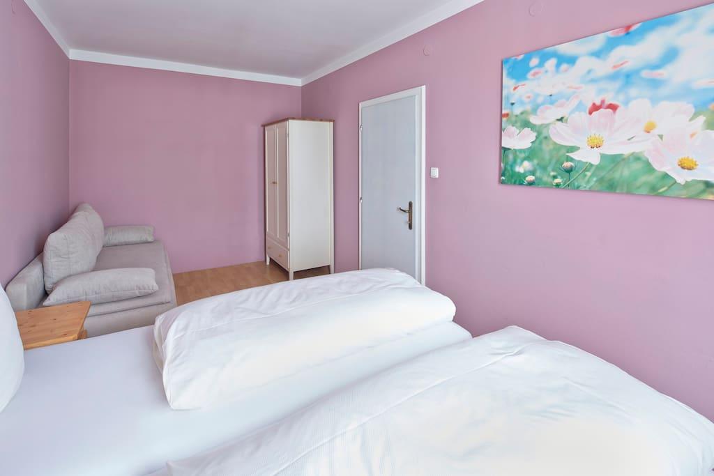 Schlafzimmer mit Bett und Schlafsofa