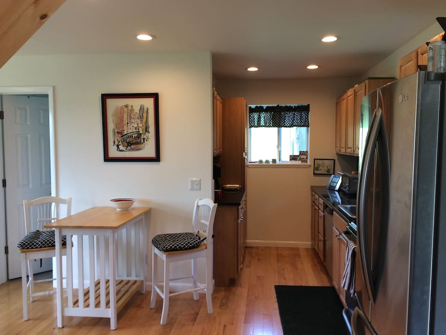 Kitchen complete with stove, refrigerator/freezer, microwave and dishwasher. Full size expandable table as well as a country table and stools.