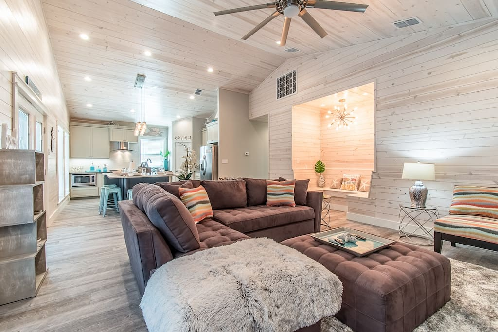 """Open-concept living area with vaulted ceilings, sectional seating for 6, and a 60"""" flat screen TV."""