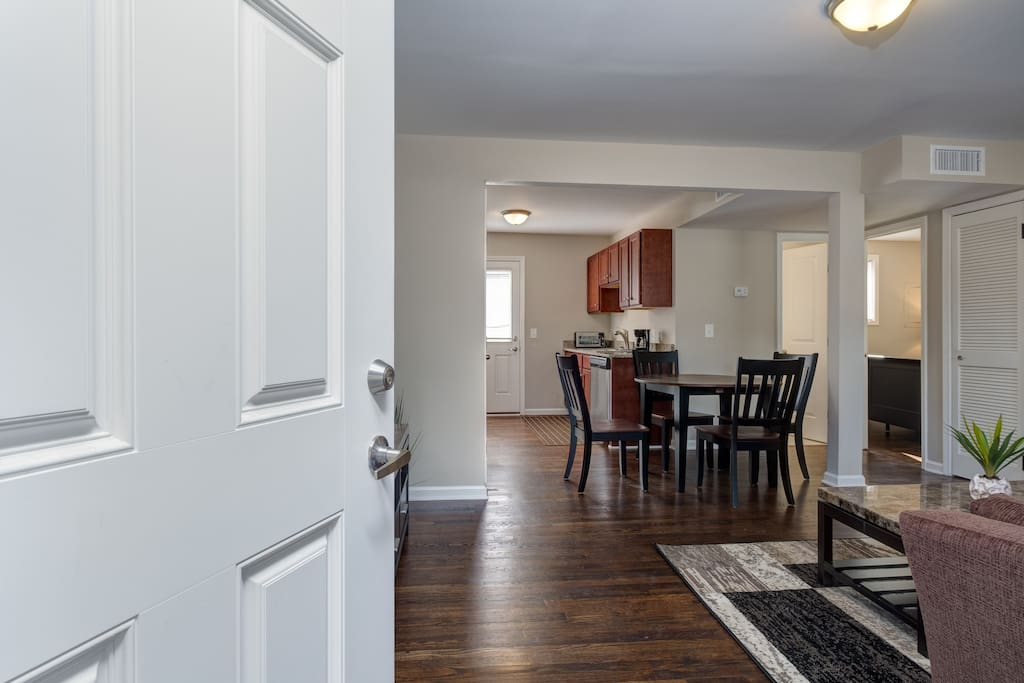 Open-concept main space flows from living room to dining area to kitchen. Professionally cleaned by housekeeping staff.
