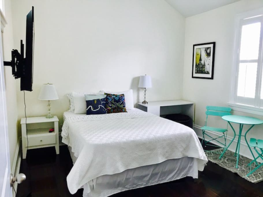 Queen size bed, smart tv, desk, and bistro table.