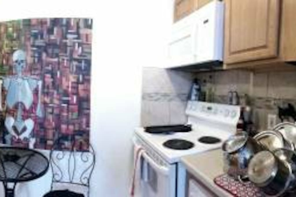 Kitchen with a bistro table, dishwasher, and all the pots, pans, and spices that you'd need to cook!