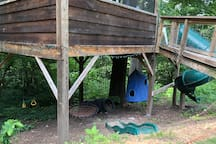 There is playground equipment under the treehouse as well. In addition to the green twisty slide, kids can also enjoy a climbing net, trapeze, spider swing, and hanging tent. Beyond here are the climbing trees and swings, which are set off in the woods slightly, but visible from the treehouse deck.