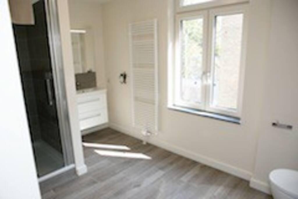 badkamer met douche, wastafelmeubel en zwevend toilet. Handdoeken aanwezig