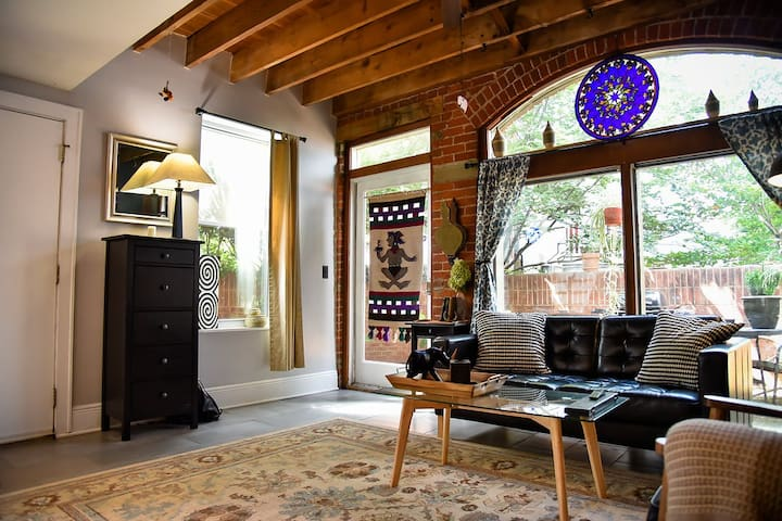 Here's the living room with plenty of natural light, exposed brick and trinkets from travels around the world.