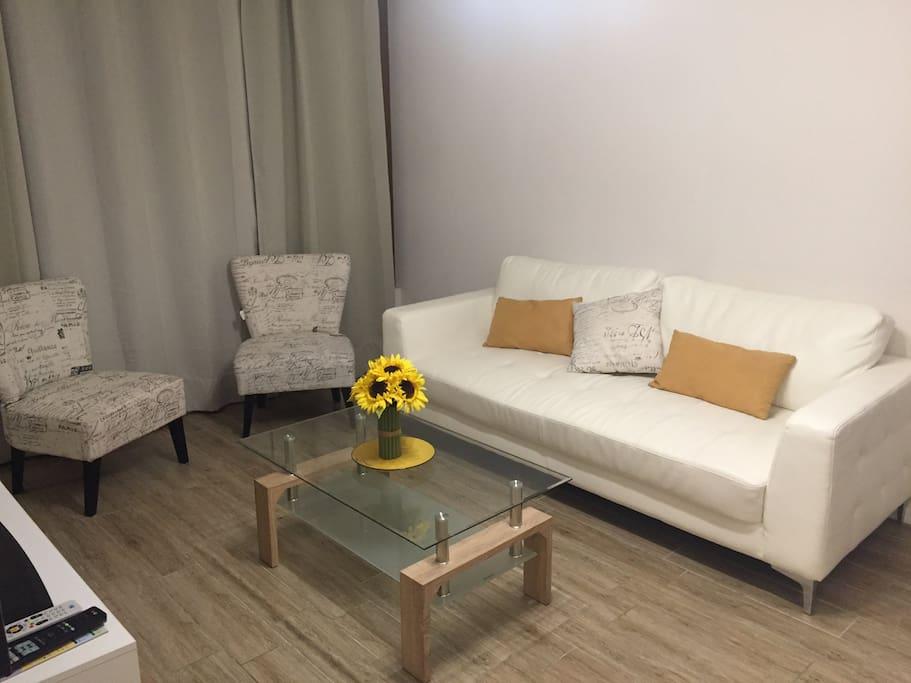 Living con sofá de 3 cuerpos y 2 sitiales, mesa de centro y Rack.