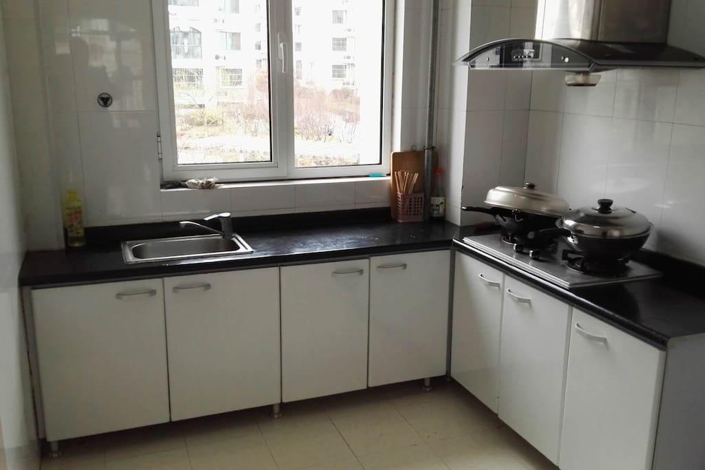 厨房有炒锅和蒸锅,冰箱。