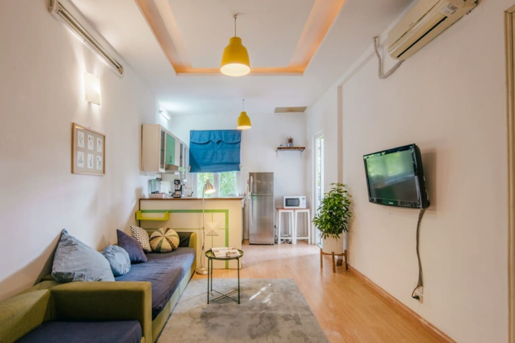 Living room with aircon and full of light together with kitchen
