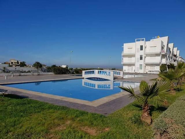 Chambre dans une résidence vue mer et piscine.