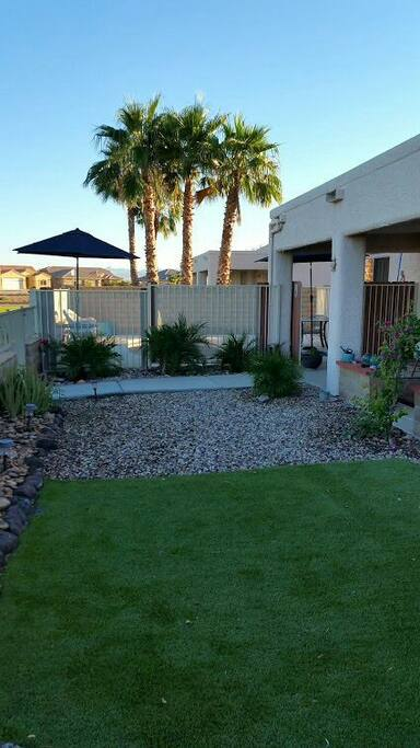 Back yard separated from pool area by security fence and lockable gate.