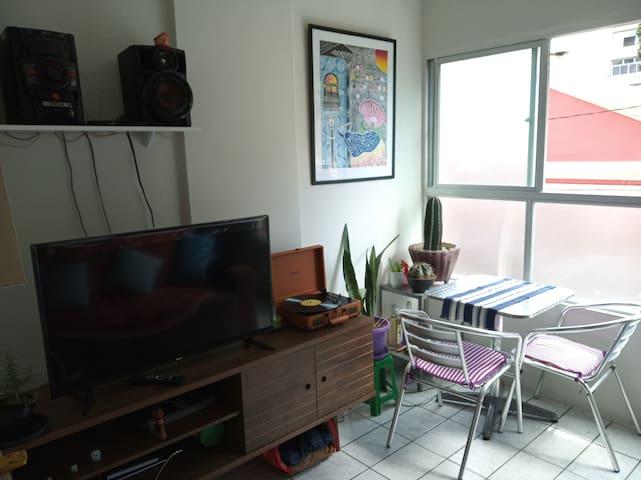 Espaço da sala, com TV, rádio, mesa e vitrola.