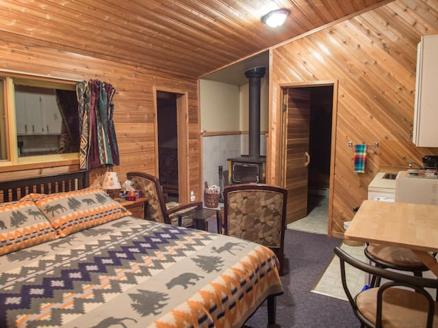 Main room with queen bed, wood stove and kitchenette.