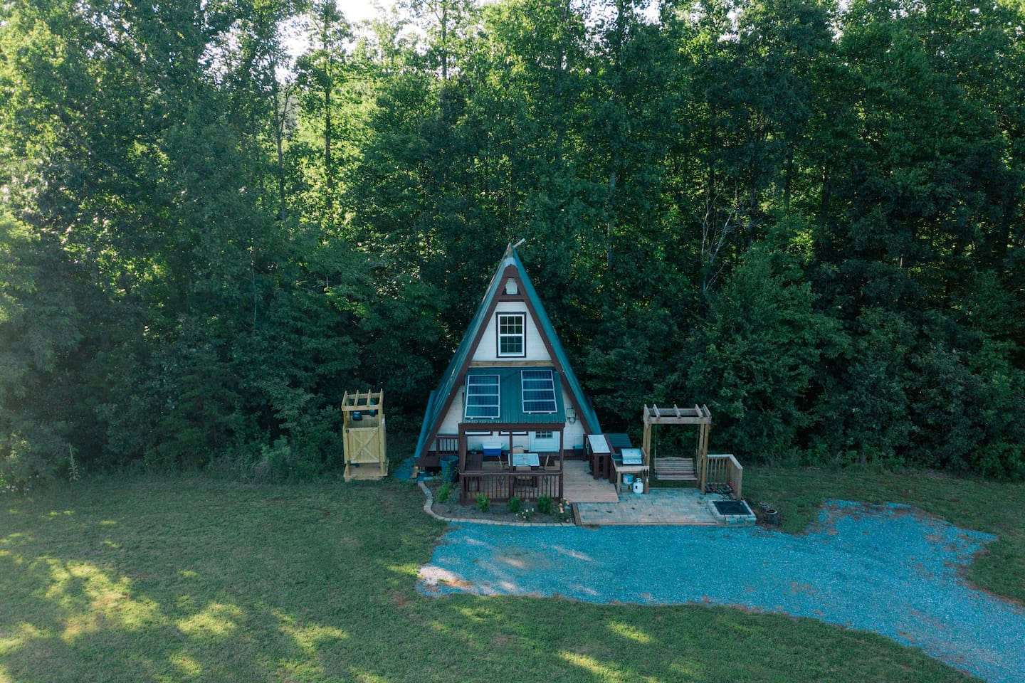 Our wonderful little A-Frame, equipped with solar power, an outdoor shower, fire pit, grill, and camp stove for cooking. Wooden swing to enjoy the quiet mornings on and evening sounds of nature.Table and chairs for outdoor seating and a wooden bench.