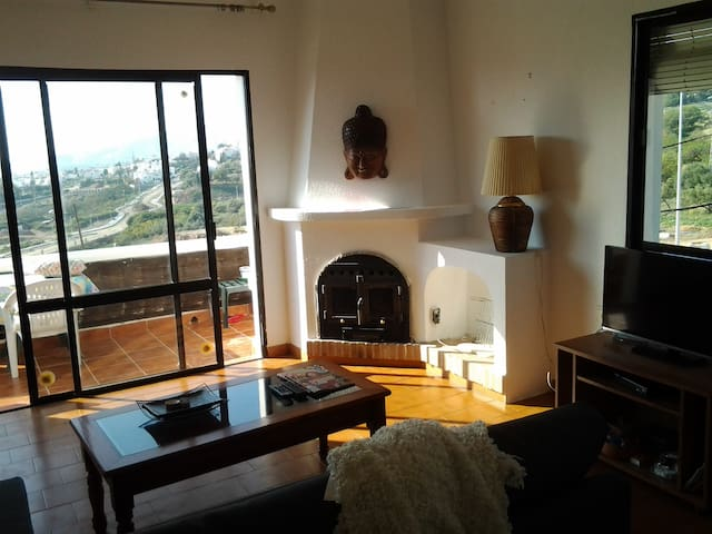 Sitting room with a double bed soffa, views of the sea, mountain and Nerja city. Wood fire place.