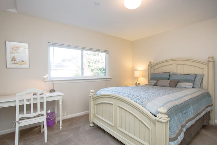 The master bedroom has a comfortable queen bed and writing desk, and overlooks the central garden and the private patio