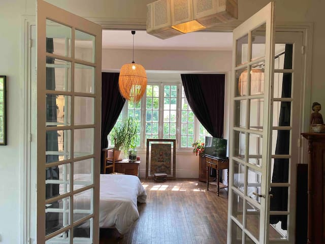 Chambre parentale lumineuse avec bow window donnant sur le jardin et le salon avec rideaux occultants  Parental sunny bedroom with bow window & garden view. Dark curtains to prevent from daylight entering the room when sleeping
